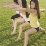Four women doing yoga in a park